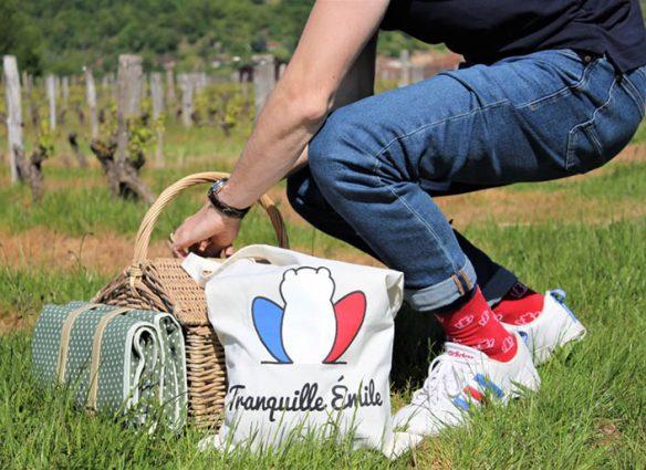 homme agroupi dans l'herbe avec panier de pique nique et tote bag Tranquille Emile