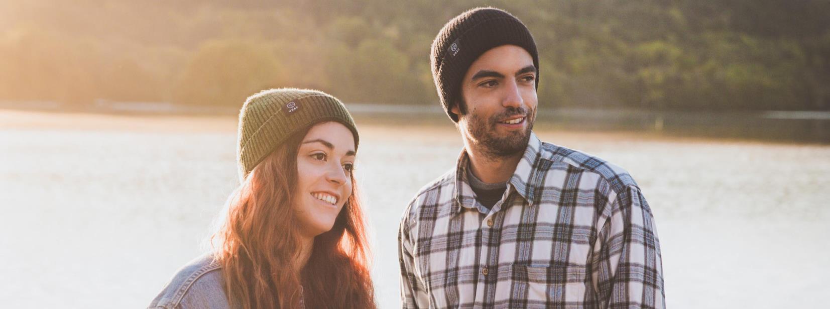 une femme et un homme devant un lac avec des bonnets en laine Ubac