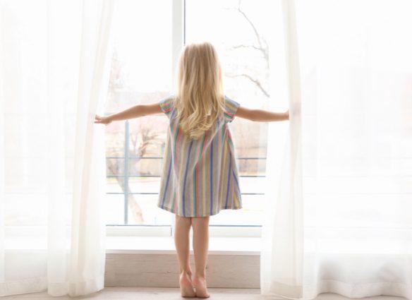 enfant ouvrant un rideau